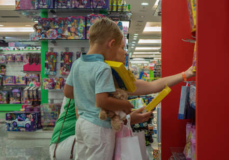 Mother and little son choosing the gifts in the toy shop. Boy is happy to get so many presents Фото со стока