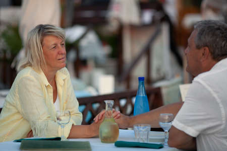 Mature couple holding hands during the romantic evening in outdoor restaurant