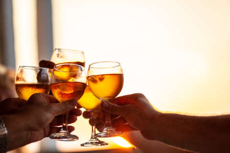 Close-up shot of friends or family raising glasses and toasting with wine against the sunset light during the celebration or party Фото со стока