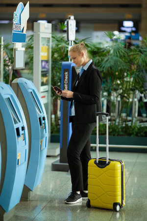 Woman with passport is going to check-in with self-service terminal at the airport