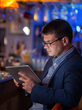 Young serious businessman is attracted with business matters in the bar. He wanted to relax but still working on digital tablet