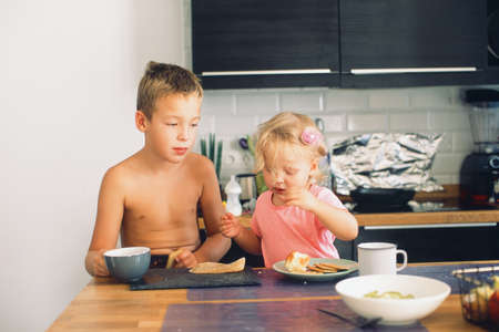 Siblings having breakfast together in the kitchen. Calm big brother watching funny baby sister