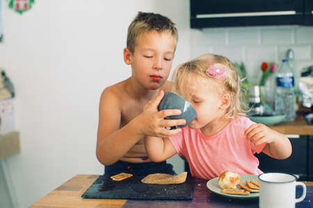 Elder brother and little sister having breakfast in the kitchen. Careful boy helping girl drink from the cup