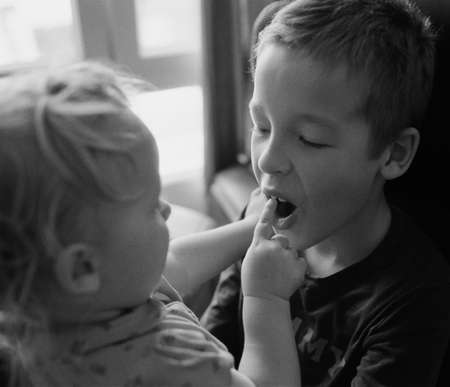 Black and white shot of siblings playing together. Little girl wants to check brothers teeth Фото со стока