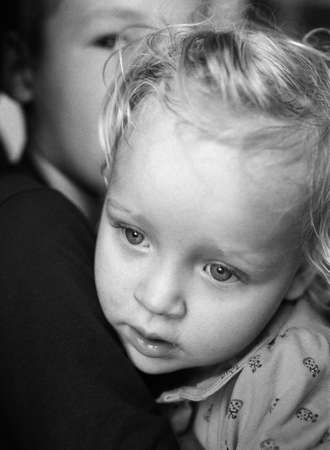Black and white close-up portrait of a quiet baby girl in the hugs of big brother. Love and taking care of close people