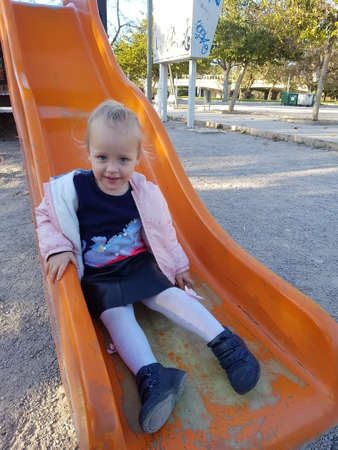 Cheerful little girl is happy to have fun on the outdoor playground. Lovely fair-haired child on the slide Фото со стока