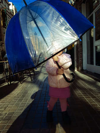 Little girl with big umbrella against the sun in the street. Child loves to hide under it