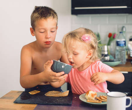 Elder brother taking care of junior sister and helping her drink from the cup during breakfast. Everyday morning moments