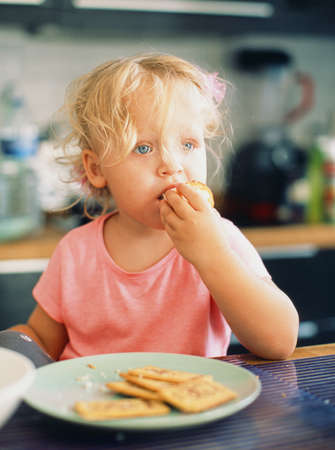 Portrait of a little girl with tousled fair hair having breakfast in the kitchen