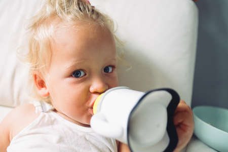 Close-up home portrait of a fair-haired girl toddler looking to the camera while drinking milk from sippy cup
