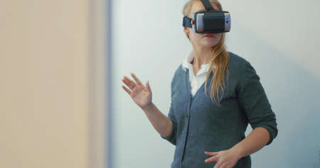 Young blonde woman playing game using VR-helmet for smart phones. Augmented reality device allows to deep into virtual space Фото со стока