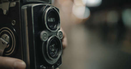 Close-up shot of a woman with retro camera making photo or video of coming subway train. Focus on the camera