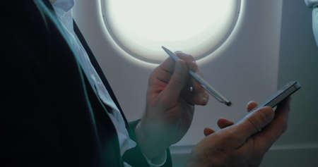 Close-up shot of a businessman using pen to type on smartphone in the plane. Communication during the flight Фото со стока