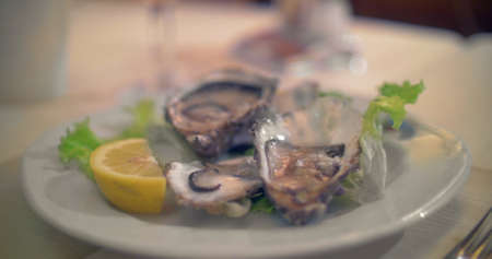 Close-up shot of pouring lemon juice on the open oysters served in restaurant. Delicious seafood Фото со стока