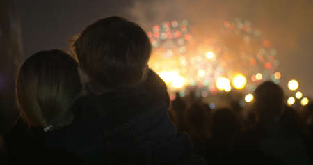 Mother holding son in arms and they enjoying bright firework show at night. Celebration in the city. Back shot