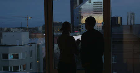 Man and woman using tablet computer standing by the window at home at night. City panorama can be seen through the glass Фото со стока