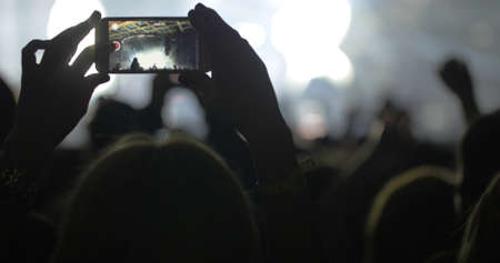 Hands in the crowd holding smart phone and shooting musical performance. Bright illumination on the stage