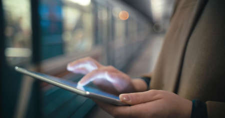 Close-up shot of female hands typing on touch pad near the leaving train at underground station. Easy way to work to communicate in any place Фото со стока