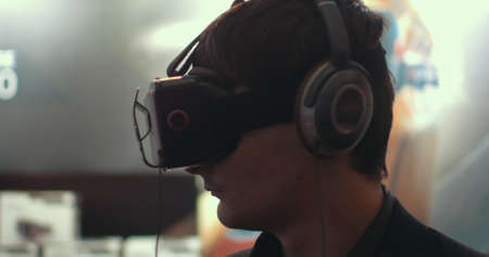 Close-up shot of a man in headphones getting experience in using VR-headset. Augmented reality device creating virtual space for smartphone applications