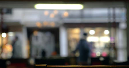 Defocused shot of people walking along the street, view through the cafe or restaurant window