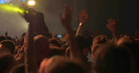 Man is taking photos of the concert using his smartphone, people around him are dancing with raised hands.