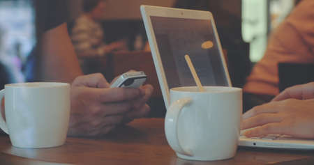 Man uses smartphohe, woman works with laptop while drinking coffee in cafe, faces are invisible