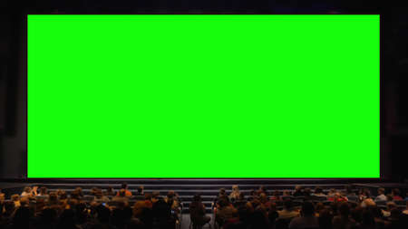 Viewers sitting in front of a big chroma key screen in the auditorium. Audience applauding, light going down Фото со стока - 150461717