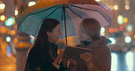 Two young women with umbrella using online map on tablet computer to find the way in the evening city