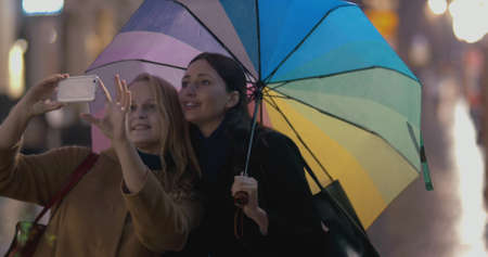 Two young girls with multicolored umbrella makes selfie on the street on rainy day, people are passing by