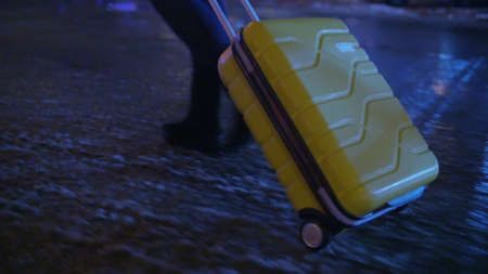 Steadicam shot of a woman with trolley bag walking alone on wet sidewalk at night. Dropping everything and going away