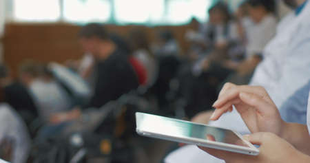 Close-up shot of female hands typing on tablet computer in auditorium during the medical lecture, conference or symposium