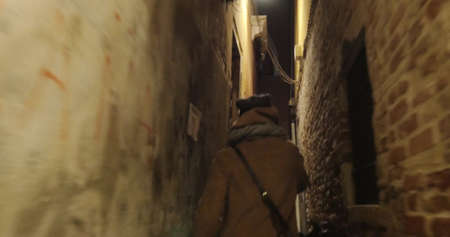 Steadicam shot of a woman with phone running at night. She escaping from maniac in dark narrow passage between old worn buildings