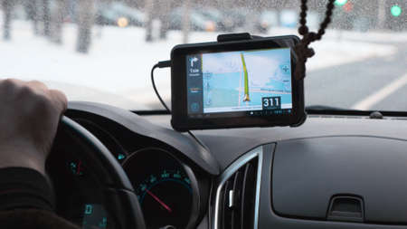 Close-up shot of car driving with GPS device over the dashboard showing a route