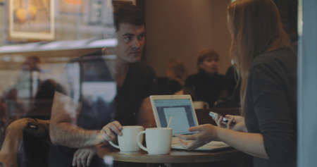 Two fiends are sitting in cafe and have lively conversation, woman is holding a smartphone and laptop is standing in front of her. Shot is made through the cafe show window.