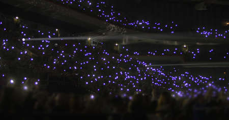 Performance in the stadium at night. Crowd of people on stands waving with small flashlights Фото со стока