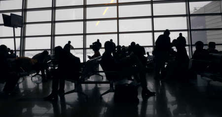 Dolly shot of people spending time in airport lounge. They waiting for their flights, some looking out the window