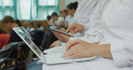 Woman and man doctors or medical students using laptop and digital tablet during the lecture or conference Фото со стока