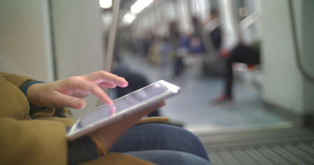 Close-up shot of a woman typing on tablet PC while traveling by underground train Фото со стока