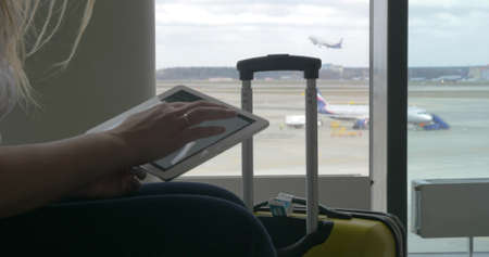Female traveler using touch pad sitting by the window at airport, suitcase standing nearby. Takeoff strip with planes in background. One airplane is getting off