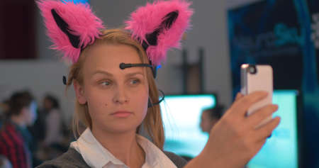 Woman wearing neuro cat ears and making selfie with a phone. This brainwave-controlled gadget showing the emotion you having at the moment with ears movement Фото со стока