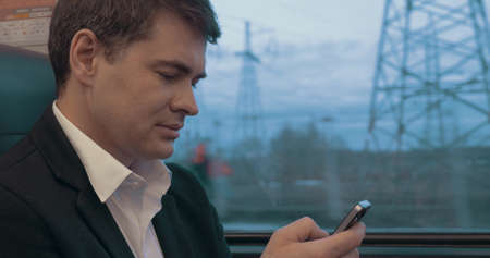 Young businessman texting on smartphone or browsing in internet while traveling by train. Communication in business trip