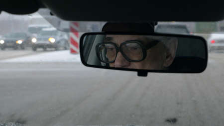 Old man in glasses driving a car. Nasty snowy day and messy roads in the city. Sometimes he looking in the rear mirror