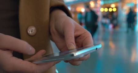 Close-up shot of female hands typing sms or chat message on smart phone at the station or airport. Defocused background with walking people Фото со стока