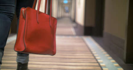 Steadicam shot of a woman walking along the corridor with big red bag in hands. Camera is following the bag.