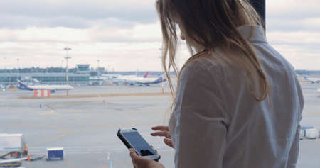 Young woman with smart phone at the airport. She sending sms and looking at the area with planes and trucks through the window. Traveler waiting for the flight