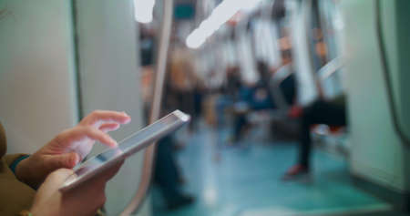 Close-up shot of a female hands using touch pad in subway train. Other passengers in blurry background