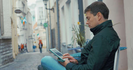 Profile view of adult man working on his tablet outdoors in small city street. Tallinn, Estonia