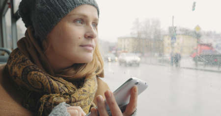 Young woman with slight smile typing sms or chat message on mobile and looking out the window while traveling by bus in the city Фото со стока