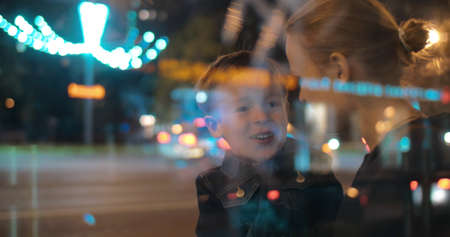 Son and mother in the busy street at night. Excited child talking to the mom, she embracing and kissing him. View through the glass