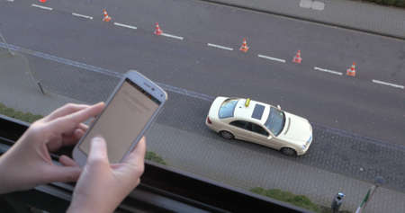Application for taxi ordering. Close-up of a woman coming up to the balcony and typing on smart phone with only hands to be seen. Taxi waiting on the road beneath Фото со стока